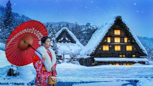 Asiatische frau, die traditionellen japanischen kimono am shirakawa-go-dorf im winter, japan trägt.