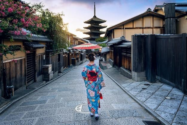 Asiatische frau, die traditionellen japanischen kimono an der yasaka-pagode und an der sannen-zaka-straße in kyoto, japan trägt.