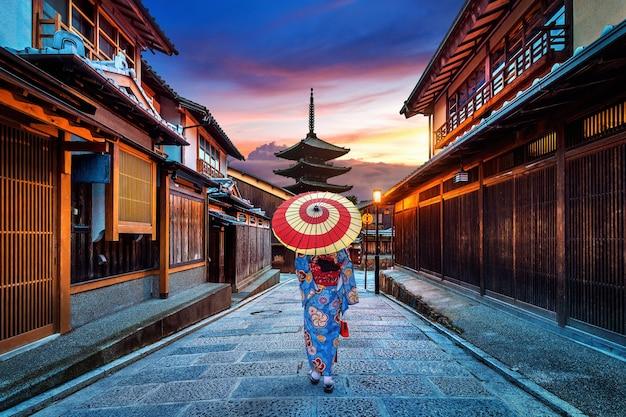 Asiatische frau, die traditionellen japanischen kimono an der yasaka-pagode und an der sannen zaka-straße in kyoto, japan trägt.