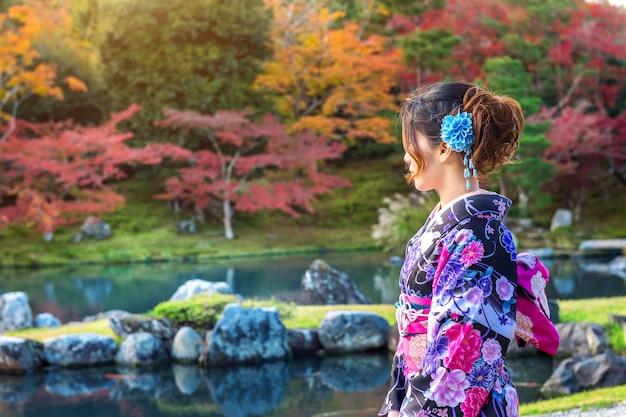 Asiatische frau, die traditionellen japanischen kimono im herbstpark trägt. japan
