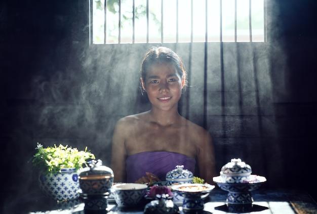 Asiatische frau, die traditionelles thailändisches kleid kostüm entsprechend kultur und tradition kocht in der küche trägt