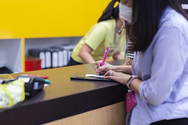 Asiatische frau, die transaktionsquittung mit an der kasse unterschreibt