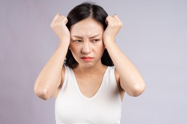 Asiatische frau, die unter kopfschmerzen leidet