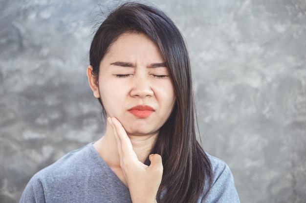 Asiatische frau, die unter zahnfleischschmerzen leidet
