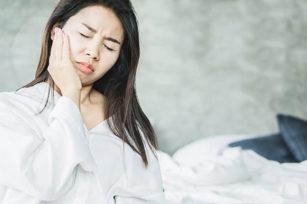 Asiatische frau, die unter zahnschmerzen leidet