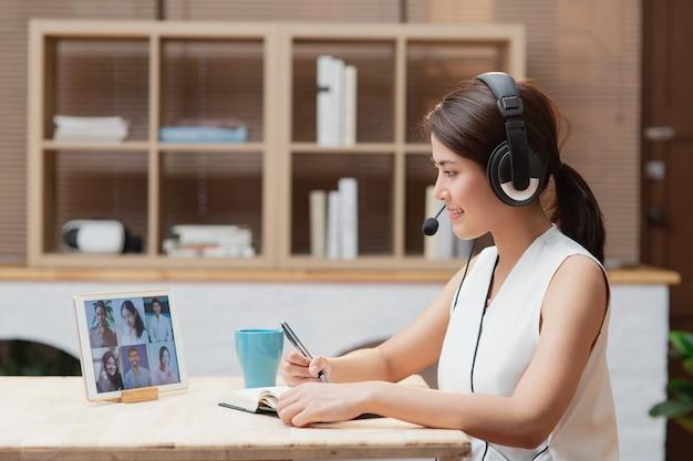 Asiatische frau, die von zu hause aus mit videoanrufkonferenz-online-treffen mit diversity-kollegenteam unter verwendung des laptops arbeitet