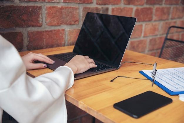 Asiatische frau, die von zu hause aus soziales distanzierendes quarantäneleute-online-besprechungsbüro arbeitet