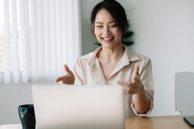 Asiatische frau, die webinar auf laptop-computer beobachtet