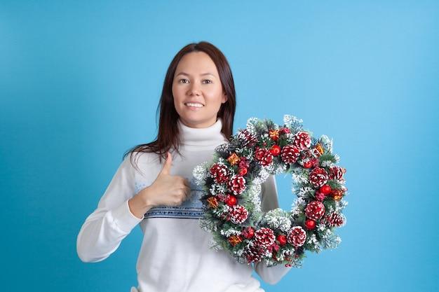 Asiatische frau, die weihnachtskranz hält