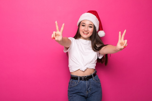 Asiatische frau, die weihnachtsmannmütze mit friedensgeste lokalisiert auf rosa wand trägt