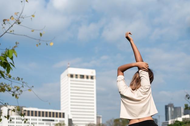 Asiatische frau, die weißes hemd in einer abklinghaltung nach dem trainieren im park trägt