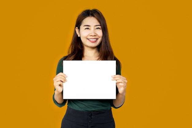 Asiatische frau, die weißes papierblatt über gelbem hintergrund hält
