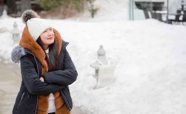 Asiatische frau, die winterlandschaft genießt