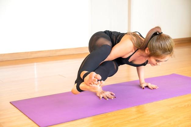 Asiatische frau, die yoga-haltung in ihrem haus im entspannenden tag tut