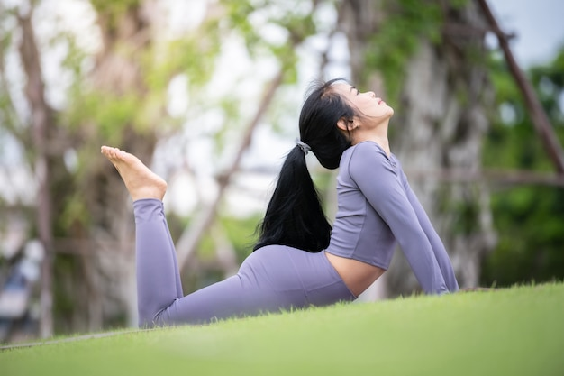 Asiatische frau, die yoga im garten praktiziert