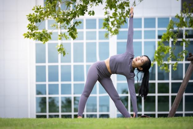 Asiatische frau, die yoga in einem städtischen garten praktiziert