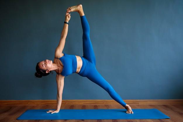 Asiatische frau, die yoga-pose auf blauer matte tut