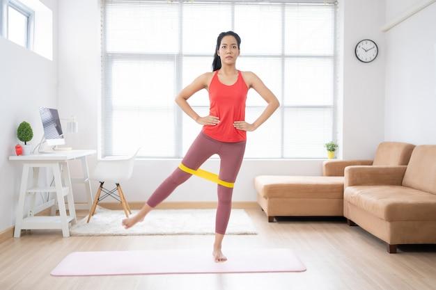 Asiatische frau, die zu hause auf einer yogamatte ausübt.