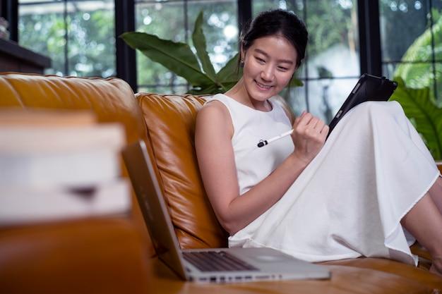 Asiatische frau, die zu hause auf sofa arbeitet