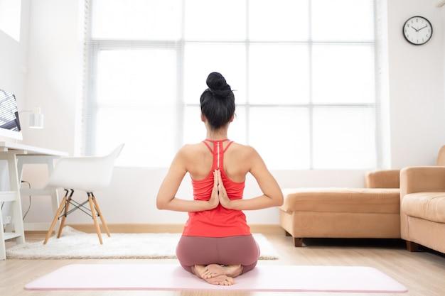 Asiatische frau, die zu hause trainiert, macht yoga