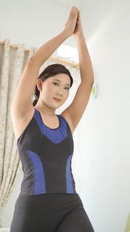 Asiatische frau, die zu hause yoga praktiziert, die handbewegung aufwärmt
