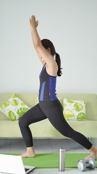 Asiatische frau, die zu hause yoga praktiziert und muskeln aufwärmt