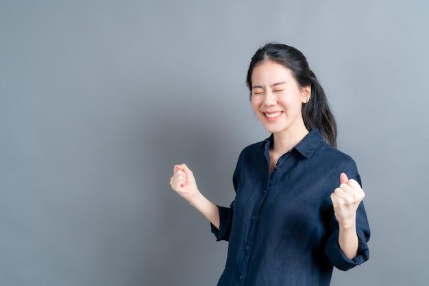 Asiatische frau freut sich über ihren erfolg und sieg und ballt vor freude die fäuste. glückliche frau, die glücklich ist, ihr ziel und ihre ziele zu erreichen. positive emotionen, gefühle auf grauem hintergrund