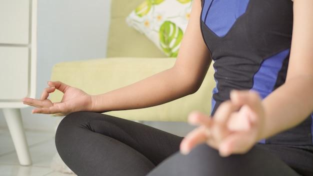 Asiatische frau genießt ihre yoga-praxis zu hause entspannend