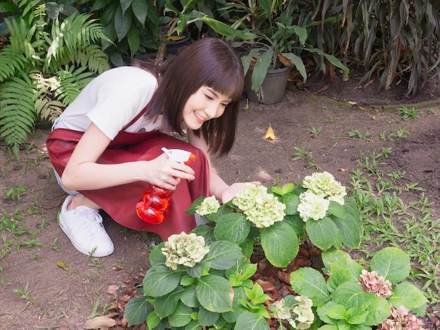 Asiatische frau gießen pflanzen
