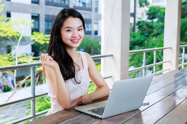 Asiatische frau glücklich verwenden ein notizbuch