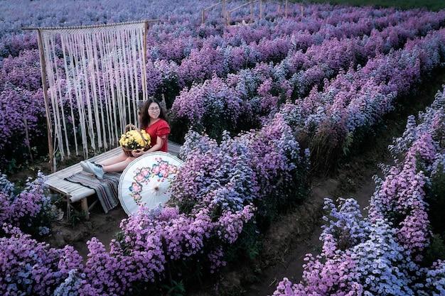 Asiatische frau glücklicher reisender mit rotem kleid hält weißen regenschirm, der in blühendem oder violettem michaelmas-gänseblümchen-blumenfeld genießt, um einen blumenkorb im naturgarten von chiang mai, thailand, zu halten