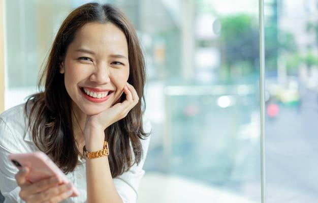 Asiatische frau hält smartphone, um anwendungsinhalte im social media-netzwerk im café kaffee zu spielen