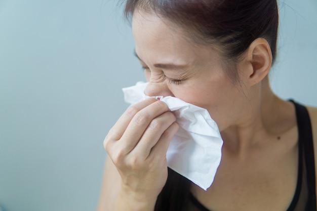 Asiatische frau hat allergische rhinitis, niesen in serviette, hat kopfschmerzen.
