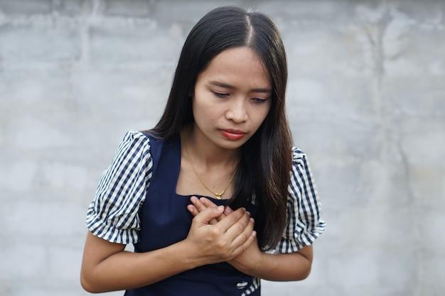 Asiatische frau hat brustschmerzen aufgrund einer herzkrankheit