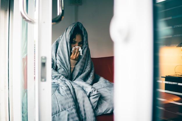 Asiatische frau hat eine erkältung, verwendet ein taschentuch, um ihren mund zu bedecken, wenn sie zu hause hustet und niest, und verhindert so die ausbreitung von virus covid 19, gesundheitskonzept. selektiver und weicher fokus.