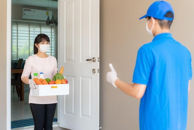 Asiatische frau holen lebensmittelschachtel mit lebensmitteln, obst, gemüse und getränken ab und daumen hoch, kontaktlos oder kontaktfrei vom lieferboten vor dem haus für soziale distanzierung für infektionsrisiko.