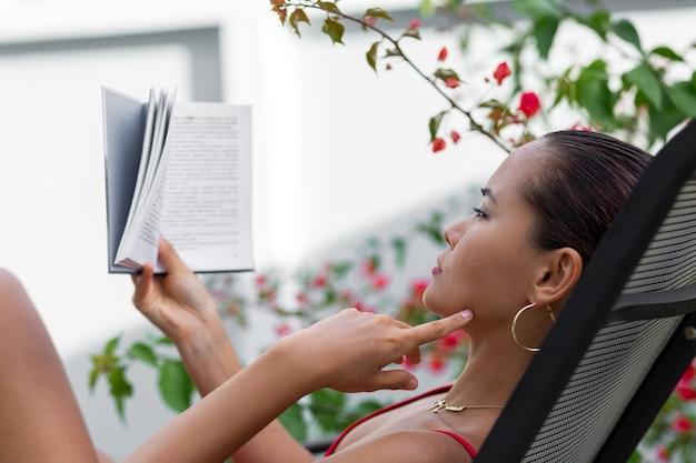 Asiatische frau im badeanzug entspannen durch pool auf sonnenliege lesen buch in der villa durch bunten blumenbaum