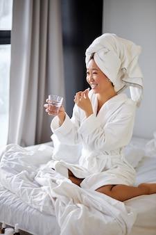 Asiatische frau im bademantel, die pillen oder vitamine mit frischem wasser, lächeln nimmt. wohlbefinden, gesundheitskonzept