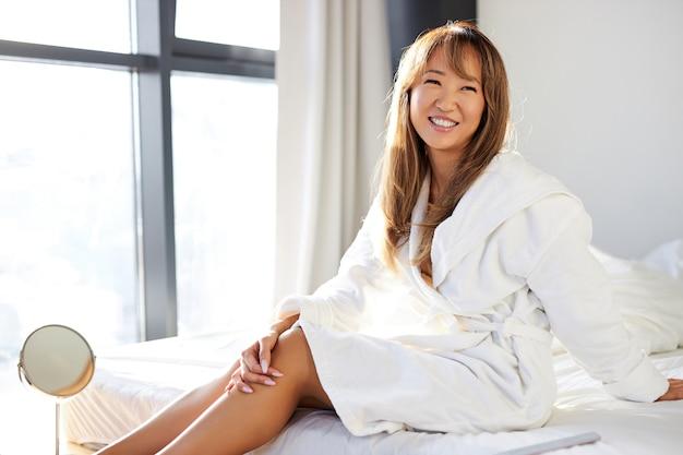 Asiatische frau im bademantel sitzt lächelnd auf dem bett im hellen schlafzimmer, genießt urlaub allein