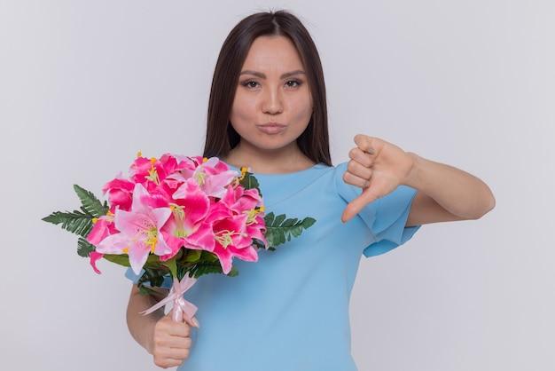 Asiatische frau im blauen kleid, das blumenstrauß hält, der vorne unzufrieden zeigt, zeigt daumen nach unten, der internationalen frauentag steht über weißer wand