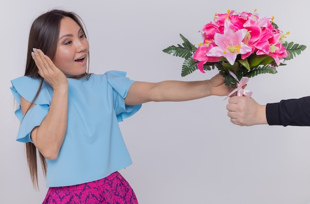 Asiatische frau im blauen kleid, das glücklich und überrascht schaut, während blumenstrauß erhalten