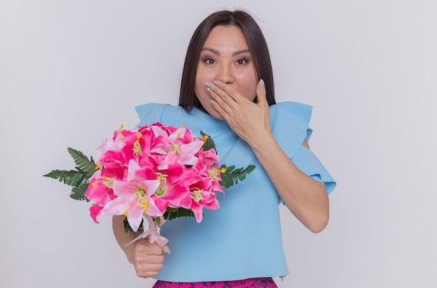 Asiatische frau im blauen kleid hält blumenstrauß glücklich und überrascht, mund bedeckend