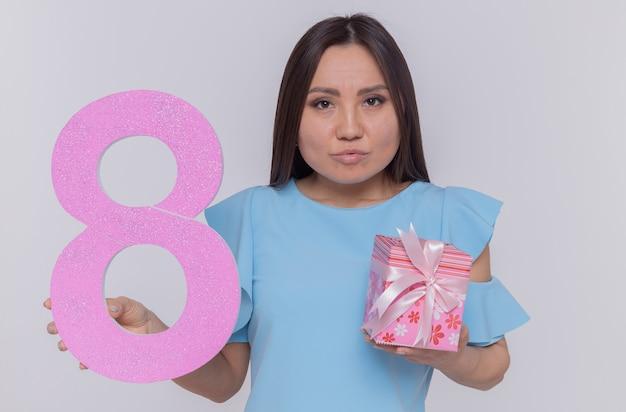 Asiatische frau im blauen kleid mit der nummer acht aus pappe und gegenwart, die vorne mit ernstem gesicht betrachtet, der internationalen frauentag feiert, der über weißer wand steht