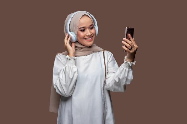 Asiatische frau im hijab, die drahtlose kopfhörer trägt, während sie auf den handybildschirm schaut