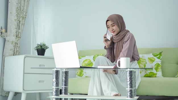Asiatische frau im hijab, die von zu hause aus arbeitet und am handy spricht