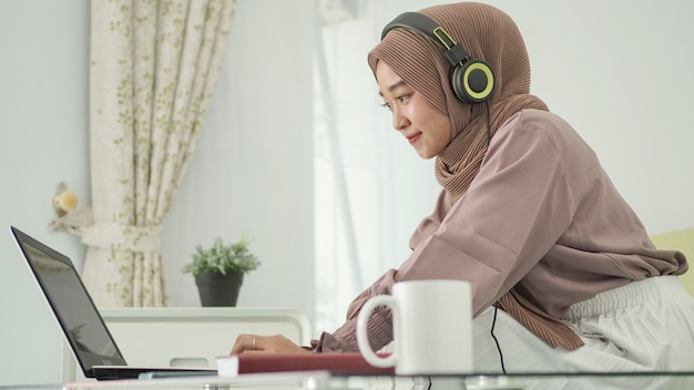 Asiatische frau im hijab, die von zu hause aus arbeitet und glücklich zuhört