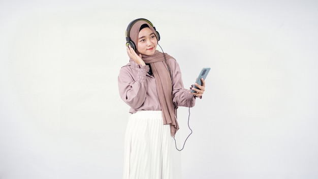 Asiatische frau im hijab hört aufmerksam zu, isoliert auf weißem hintergrund