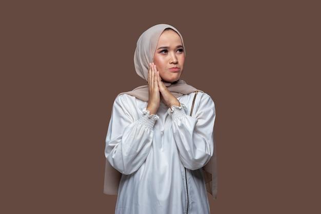 Asiatische frau im hijab mit besorgtem und enttäuschtem gesichtsausdruck