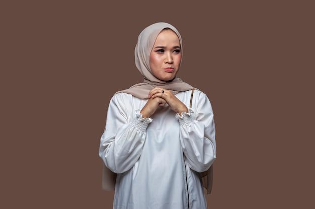 Asiatische frau im hijab mit traurigem, besorgtem und enttäuschtem ausdruck