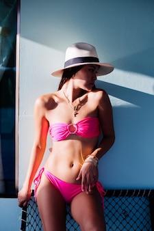 Asiatische frau im rosa bikini steht vor haus auf blauer wand